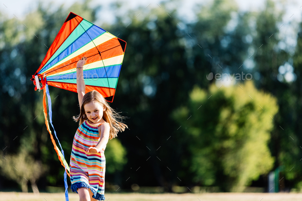 Smiling little girl playing with a colorful kite in the park. - Stock Photo - Images