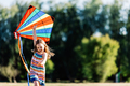 Smiling little girl playing with a colorful kite in the park. - PhotoDune Item for Sale