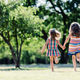 Two little girls running in the park, holding hands. - PhotoDune Item for Sale