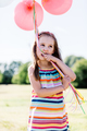 Little girl chewing balloon strings in her mouth - PhotoDune Item for Sale