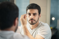 Latino Man Trimming Eyebrow For Body Care In Bathroom - PhotoDune Item for Sale