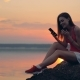 Happy Girl Sits Near Lake with Her Phone - VideoHive Item for Sale