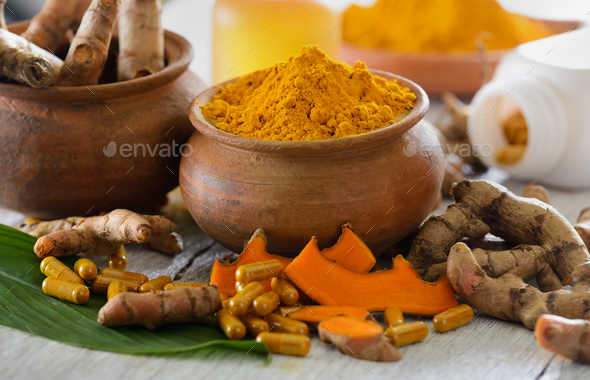 Turmeric powder and turmeric capsules on wooden background - Stock Photo - Images