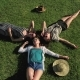 Three Girls Lying on Green Grass and Having Fun on a Meadow Sunny Day - VideoHive Item for Sale