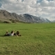 Two Happy Female Friends Lying on in the Green Grass Against the Background of the Mountains - VideoHive Item for Sale