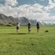 Group Of Friends Hold Hands And Run Away From Camera Toward Mountain - VideoHive Item for Sale