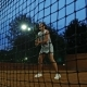 Playing Tennis at Night. Young Girl Blocking the Ball with the Tennis Racket During the Training - VideoHive Item for Sale