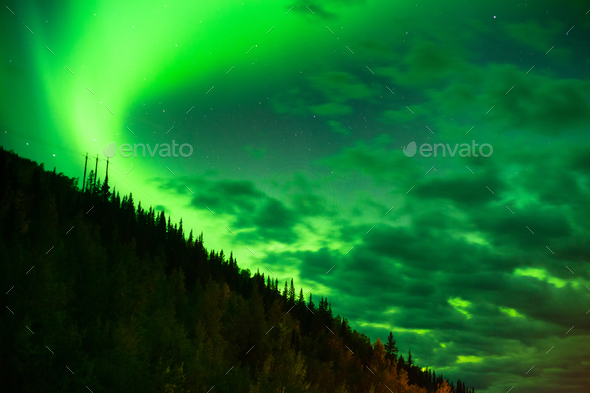 The Northern Lights Shine Up over a Mountainside near Valdez Alaska - Stock Photo - Images
