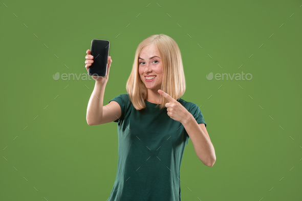 Portrait of a confident casual girl showing blank screen mobile phone - Stock Photo - Images