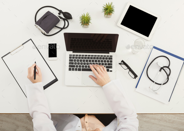 Doctor sitting at office desk, top view - Stock Photo - Images