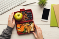 Woman eating healthy sandwich from lunch box at her working table - PhotoDune Item for Sale