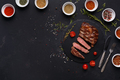 Rib eye steak and spices on black background - PhotoDune Item for Sale