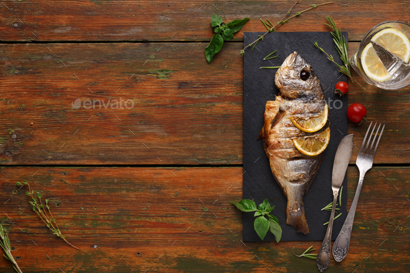 Whole grilled dorado with lemon slices on wood - Stock Photo - Images