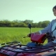 Adult Woman Driving a Quad Bike in a Field Drives Out on a Country Road - VideoHive Item for Sale