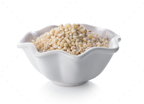 Heap of pearl barley in a bowl on white background - Stock Photo - Images