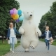 Mom and Daughter and a Polar Bear Are Having Fun Along the Street. Children's Holiday Concept - VideoHive Item for Sale