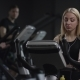 Girl in Black Sport Clothes Works Out on a Bike at Gym - VideoHive Item for Sale