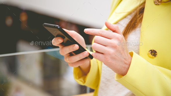 Female uses smart phone in shopping center - Stock Photo - Images