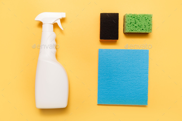 White plastic hand spray bottle with sponges on yellow background - Stock Photo - Images