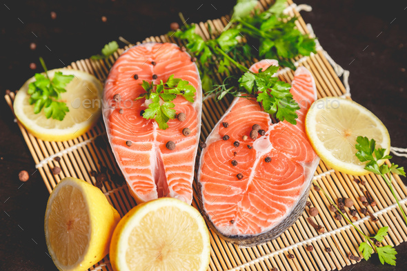 Salmon steaks with lemon, spices and spoon with salt - Stock Photo - Images
