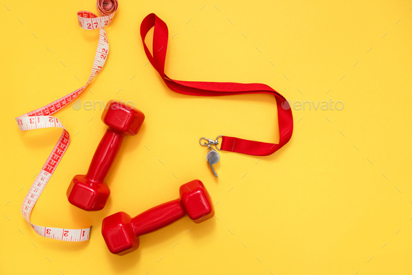 Two red dumbbells, tape measure and whistle - Stock Photo - Images