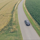Aerial View of Black Car Driving Through Fields - VideoHive Item for Sale