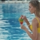 Pretty Girl in Yellow Swimsuit Relaxes at Swimming Pool and Drinks Cocktail - VideoHive Item for Sale