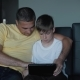 Father and Son Are Sitting on the Sofa Watching Movies and Playing Games on the Tablet. A Happy - VideoHive Item for Sale