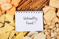 Inscription unhealthy food in notebook and heap of crisps and cookies - PhotoDune Item for Sale