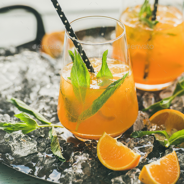Refreshing cold alcoholic summer cocktail with orange, peppermint and ice - Stock Photo - Images