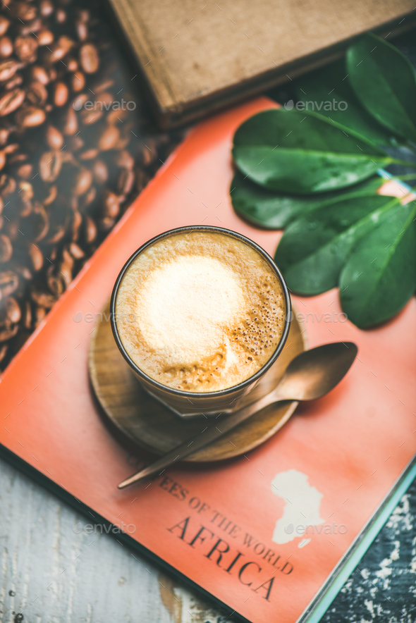 Cappuccino coffee in glass over table with bright magazine background - Stock Photo - Images