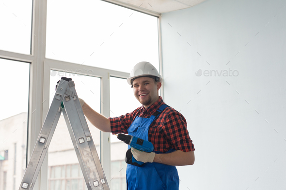 Man with screw gun or screwdriver, Building master, carpenter working with drilling machine - Stock Photo - Images