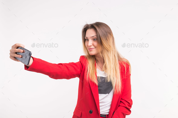 Selfie making beautiful young woman in red jacket - Stock Photo - Images