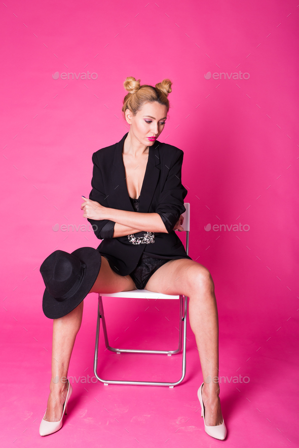 Woman wearing black hat. Fashion studio portrait over pink background - Stock Photo - Images