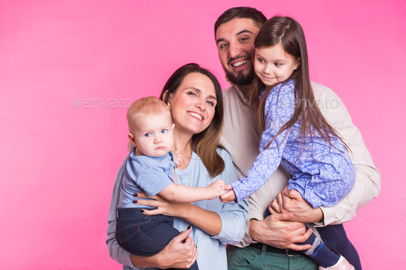 Happy mixed race family portrait smiling on pink background - Stock Photo - Images