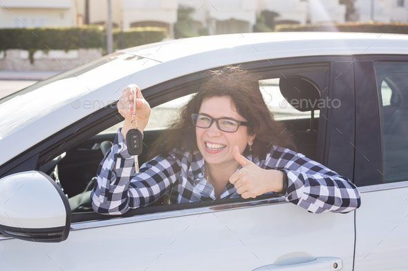 Young woman in car shows thumbs up and key - Stock Photo - Images
