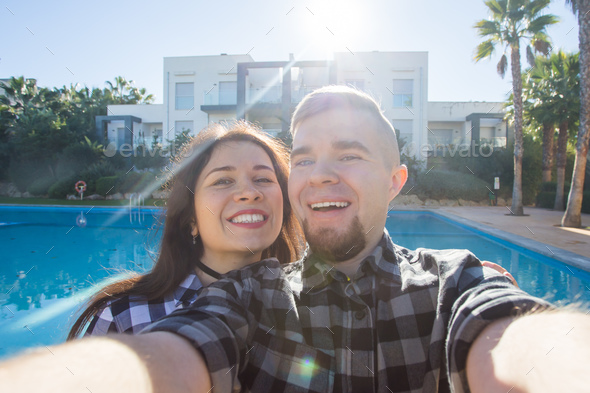 Travel, vacation and holiday concept - Young couple selfie smartphone photo near a swimming pool. - Stock Photo - Images