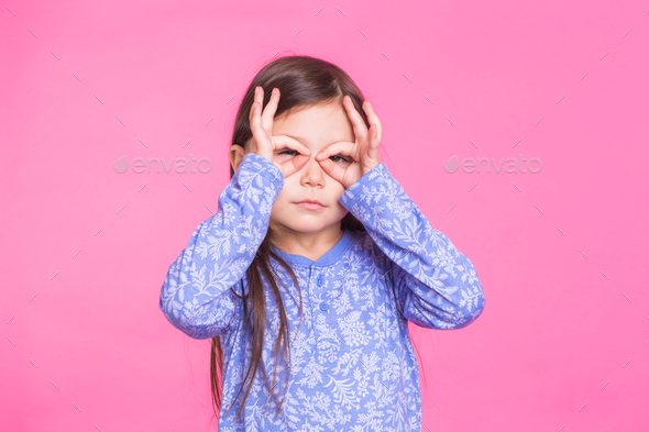 Funny funky delightful cute baby child girl making glasses with fingers fooling around - Stock Photo - Images