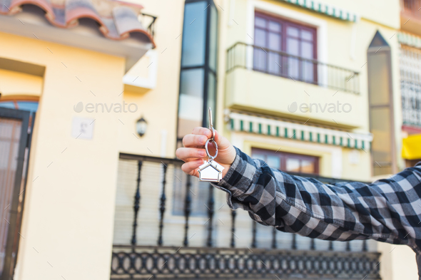 Holding house keys on house shaped keychain in front of a new home. - Stock Photo - Images