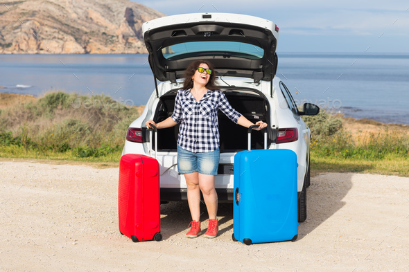 Young woman standing near back of car smiling and getting ready to go. Summer road trip - Stock Photo - Images