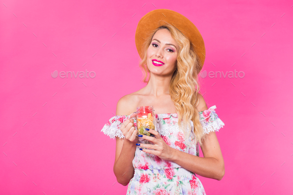 Young beautiful woman with fruit jar on pink background with copyspace - Stock Photo - Images