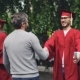 Smiling Graduating Student Is Shaking His Father's Hand and Hugging Him - VideoHive Item for Sale