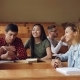 Careless Girls and Boys Are Talking and Laughing Sitting at Desks in Lecture Hall, Students Are - VideoHive Item for Sale