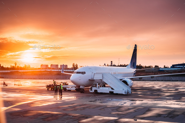 Aircraft Plane Boarding Passengers In Airport In Sunny Sunset Su - Stock Photo - Images