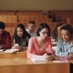 Young People Are Using Smartphones and Talking Sitting at Desks in Lecture Hall at University - VideoHive Item for Sale