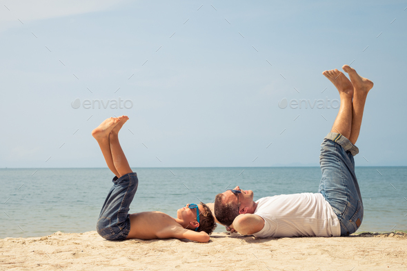 Father and son playing on the beach at the day time. - Stock Photo - Images