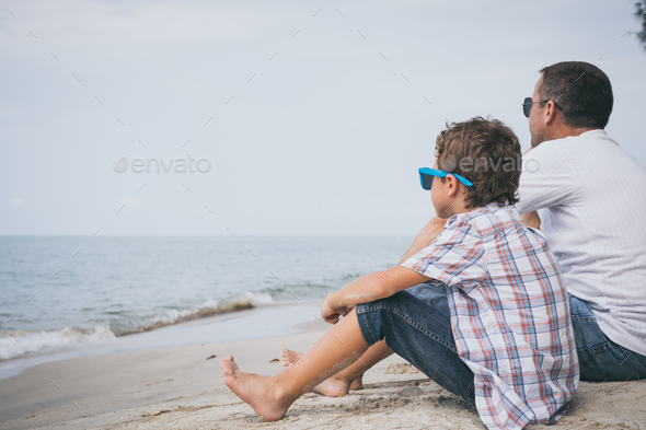 Portrait of young sad little boy and father sitting outdoors at - Stock Photo - Images