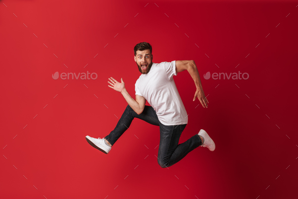 Handsome excited young man running - Stock Photo - Images