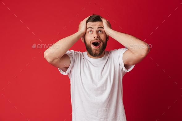 Excited young handsome man looking aside. - Stock Photo - Images