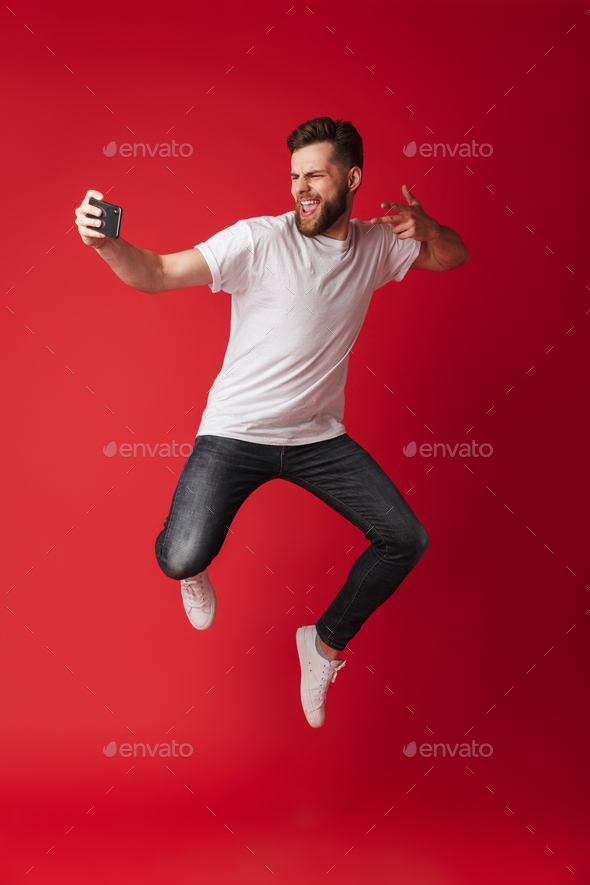 Excited young man make selfie by mobile phone jumping. - Stock Photo - Images